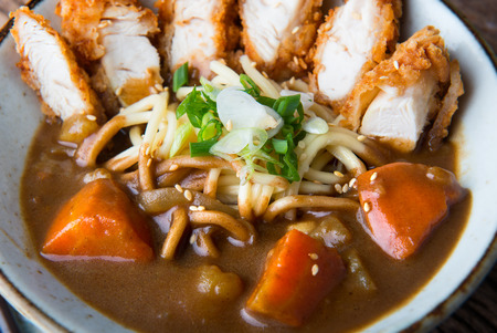Japanese curry with udon noodle and crispy chicken tenderloid in bowl cup style ready to serve. Stock Photo
