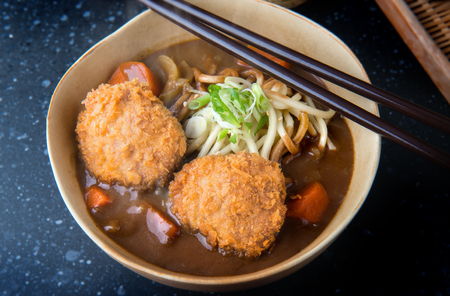 Japanese curry with udon noodle and crispy pork chop croquettes topping on bowl cup style.