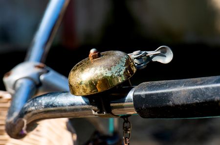Retro and old style brass metal bicycle bell in sunshine lighting.