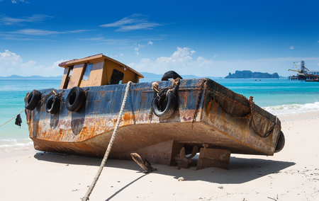 Out focus of old and rusty vintage boat on the beach with outdoor sun lighting.