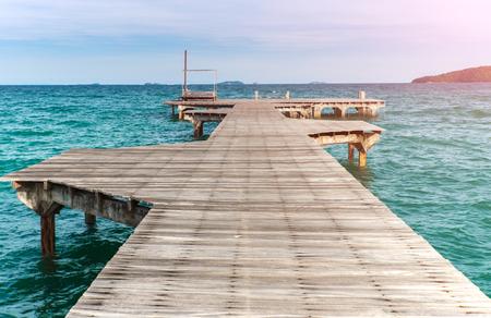 Long wooden sea bridge with outdoor sun lighting.