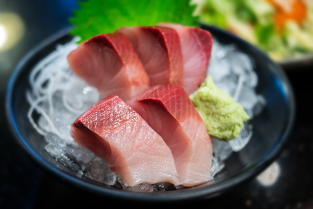 Raw Yellow tail fish or Hamachi sashimi in Japanese food name photo with very low lighting and wide aperture. 스톡 콘텐츠