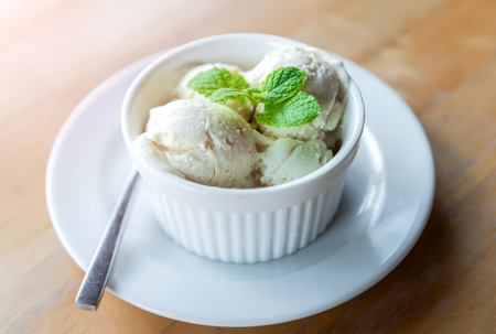 Milk vanila ice creams with mint leaf  in white cup with morning warm lighting. Stockfoto