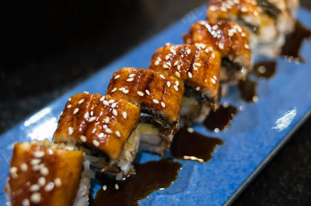 Japanese unagi eel grilled sushi maki roll cutting with indoor low and dark lighting in low focus.