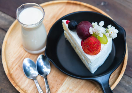 Sweet fruit cream cake cut serve with milk glass set on wooden plate with indoor low lighting.