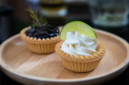 Mini tartes aux fruits et à la crème dans une assiette en bois avec un faible éclairage intérieur. Banque d'images