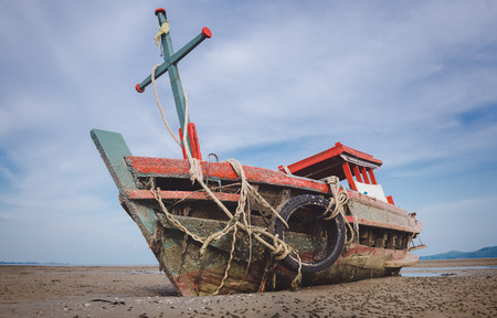 Wreck wooden fishery boat on the beach with blue and cloud sky.