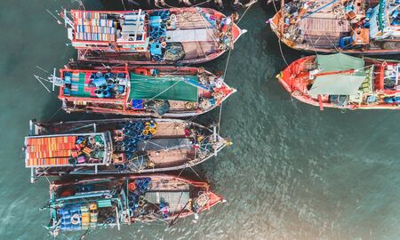 Top view from sky of group of wooden fishery boat at the sea marina with day lighting.