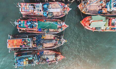 Vista dall'alto dal cielo di un gruppo di barche da pesca in legno al porto turistico con illuminazione diurna.