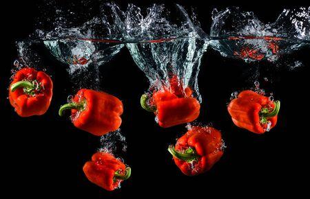 Agua goteando pimiento rojo o pimentón con salpicaduras de agua en fondo negro.