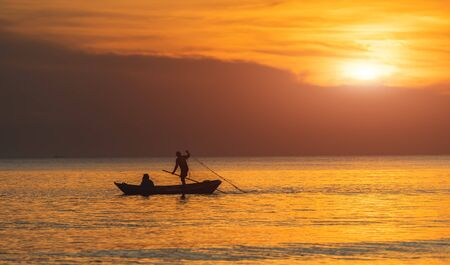 Silhouette of boat and fisherman with warm and sunset low lighting dark shadow view.