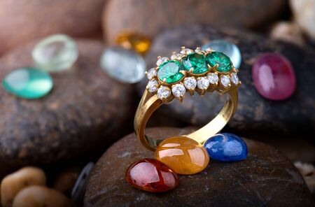 Jewelry ring and round cut mineral gemstones with dark stones background.