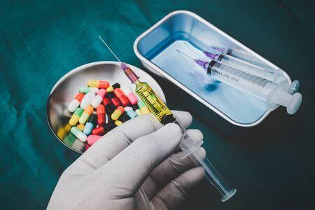 Hypodermic Syringe in white glove hand with dark background.