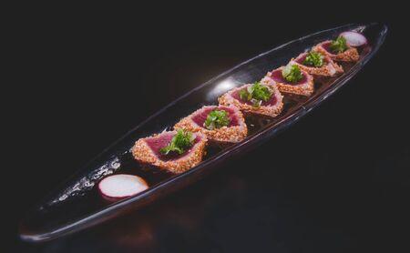 Tuna tataki arranging in the long dish with studio lighting.