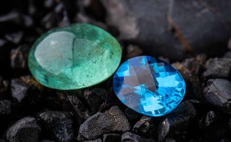 Emerald gemstone and blue quartz with dark rock background.
