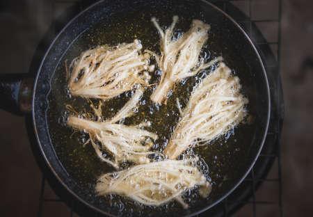 Frying crispy enoki mushroom with cooking oil. Archivio Fotografico