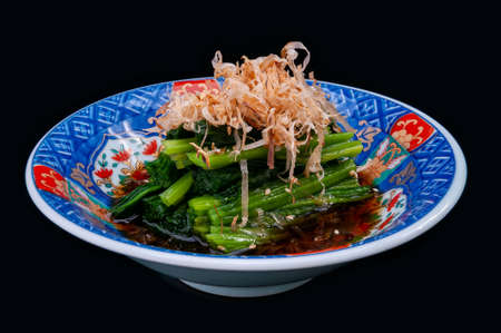 Japanese style boiled spinach in shoyu sauce with black background.
