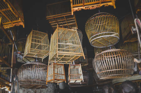 Bamboo basketry bird cage stock shop with indoor low lighting. Stockfoto