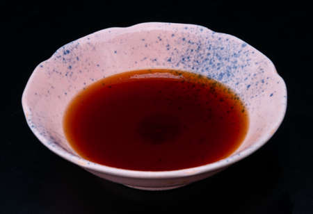 Soy bean sauce Japanese shoyu in asian style cup with black background. Archivio Fotografico