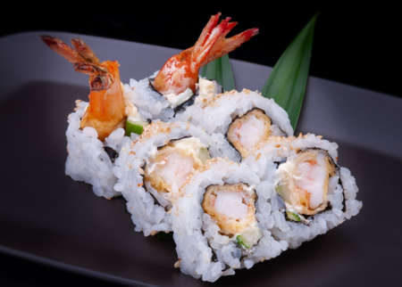 Japanese sushi roll with shrimp tempura in black background. Archivio Fotografico