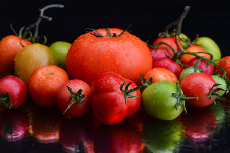 Group tomatoes with black background and reflection. Archivio Fotografico
