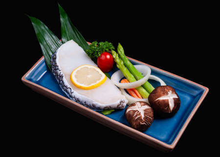 Black cod fish fillet cut in Japanese teppanyaki gindara set with dark background. Archivio Fotografico