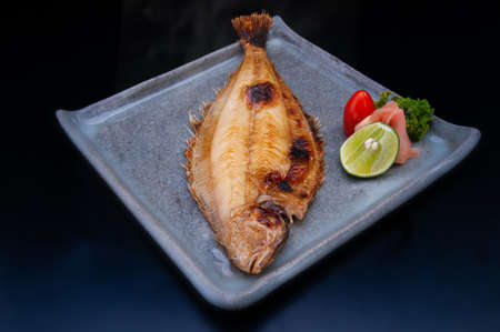 Japanese karei fish grilled in plate and lemon with dark background. Archivio Fotografico
