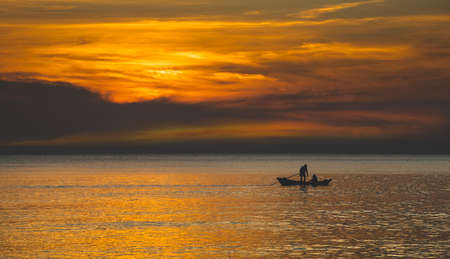 Silhouette of fishery wooden boat with warm and sunset low lighting dark shadow view. Archivio Fotografico