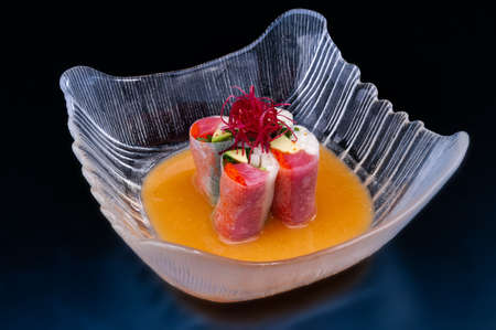 Japanese tuna fresh spring rolls with orange juice in glass bowl.