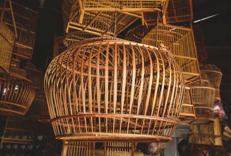 Bamboo basketry bird cage stock shop with indoor low lighting. Archivio Fotografico - 153217644