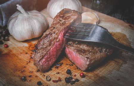 Medium rare beef steak cut slice on wooden plate with low lighting. Archivio Fotografico