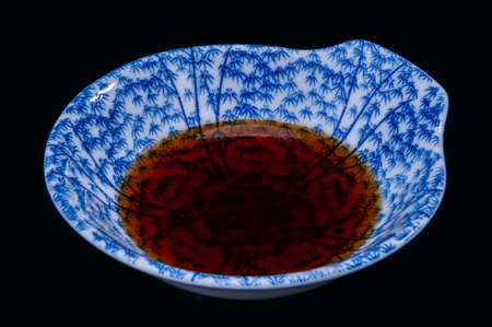 Soy sauce Japanese shoyu in asian style cup with black background. Archivio Fotografico