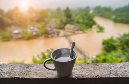Hot coffee and river nature view with morning sun lighting.