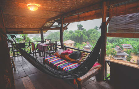 Relax hammock and bed with nature view from wooden balcony in low lighting and dark shadow.