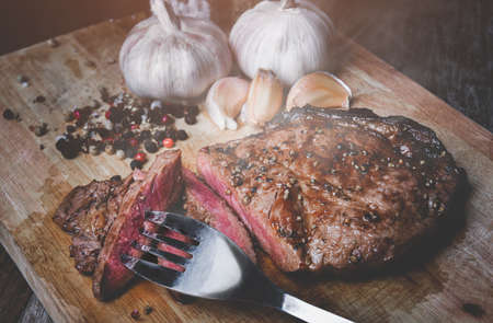 Medium rare beef steak cut slice on wooden plate with low lighting. Archivio Fotografico