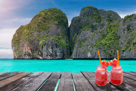 Maya bay island view with wooden board and cold drink glass in sun lighting.