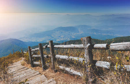 Mountain dry meadow ,fog cloud scape and wooden fence and walkway. Archivio Fotografico - 155336616
