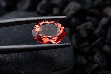 Oval red garnet gemstone with dark blackground.