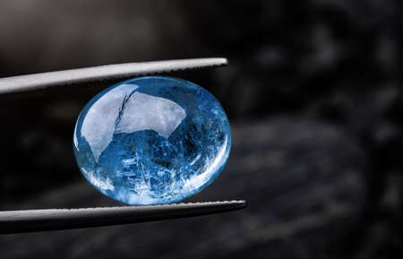Indigo blue sapphire gemstone with dark rock background. Archivio Fotografico