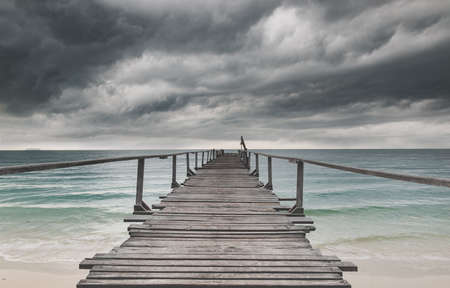 Wooden bridge and the sea with dark rain cloudy low lighting. Archivio Fotografico