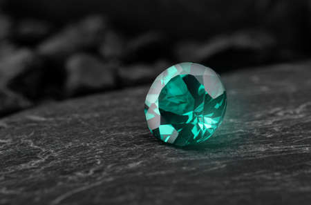 Green emerald oriental sapphire gemstone with dark rock background.