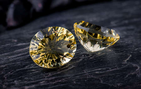 Oval Yellow gemstone sapphire with dark rock background.