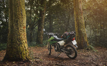 Adventure traveling enduro motocycle in mountain forest with low lighting and dark shadow.