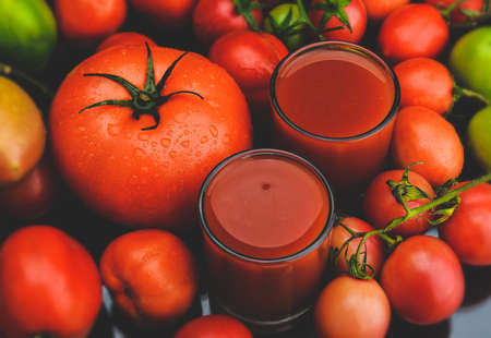Mix tomatoes and juices in glass with black background lowlighting.