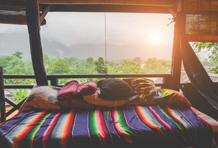 Relax bed and pillows with nature view from wooden balcony in the mist fog low lighting and dark shadow.