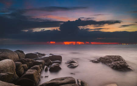 The stones in the sea with cloud sky in sunset time lighting and dark shadow..