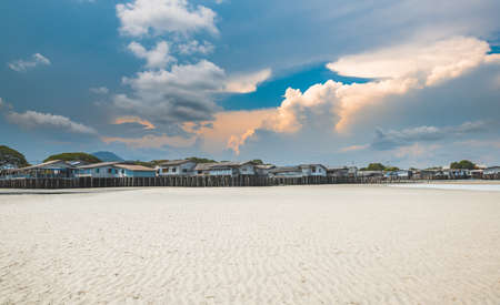 White sand beach and bay coast village with clouds and blue sky sun lighting.