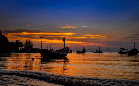 Silhouette fishery boats in the sea with sunset warm low lighting and dark shadow. 版權商用圖片 - 163963105