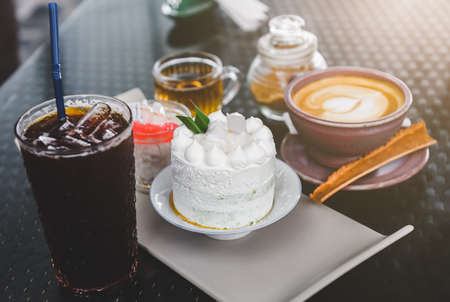 White coconut cake set and coffee  with indoor lighting. Banco de Imagens