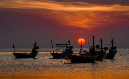 Silhouette fishery boats in the sea with sunset warm low lighting and dark shadow. 版權商用圖片 - 163963349